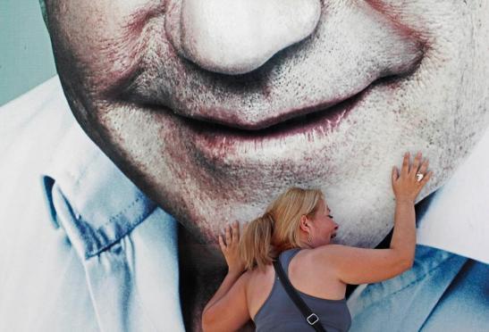 Una mujer llora la muerte de Lino Oviedo Silva, frente a un cartel del líder de Unace. Foto: René González